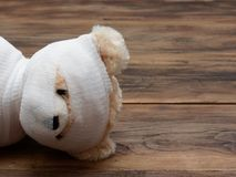 Портрет выстрела в голову милой связи куклы плюшевого медвежонка мумии с белыми марлей или повязкой на темной деревянной предпосы стоковые изображения