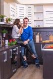 Портрет влюбчивых пар с едой в кухне Стоковые Изображения RF