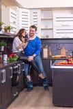 Портрет влюбчивых пар с едой в кухне Стоковая Фотография