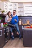 Портрет влюбчивых пар с едой в кухне Стоковые Фотографии RF