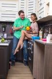 Портрет влюбчивых пар с едой в кухне Стоковое Изображение RF