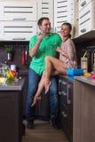 Портрет влюбчивых пар с едой в кухне Стоковое фото RF