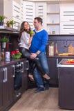 Портрет влюбчивых пар с яблоком в кухне Стоковые Изображения