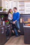 Портрет влюбчивых пар с яблоком в кухне Стоковая Фотография