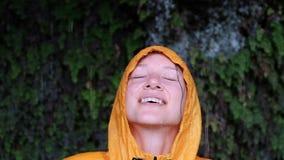 Портрет голубоглазой девушки в желтом пальто дождя поднимает голову, закрывает глаза и улыбки видеоматериал