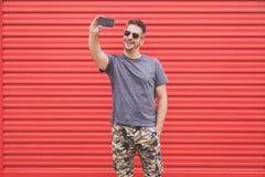 Портрет городского битника принимая автопортрет с smartphone на красной предпосылке стоковое фото rf