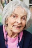 Портрет голов и плечи усмехаясь старшей женщины дома Стоковое фото RF