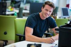 Портрет график-дизайнера работая на его столе Стоковое Фото