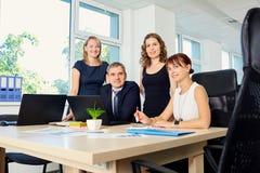 Портрет группы в составе бизнесмены и женщины в офисе позади Стоковые Фото
