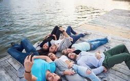 Портрет группы в составе молодые люди сидя на краю пристани, outdoors в природе Друзья наслаждаясь игрой на Стоковое Изображение RF