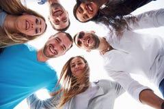 Портрет группы в составе молодые люди сидя на краю пристани, outdoors в природе Друзья наслаждаясь игрой на Стоковая Фотография