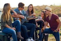 Портрет группы в составе друзья играя гитару и выпивая пиво стоковые фото