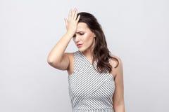 Портрет грустного теряет красивую молодую женщину брюнета с макияжем и striped положением платья и рука удержанием на ее лбе стоковые изображения