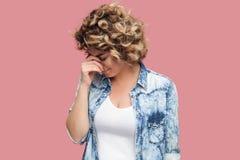 Портрет грустной самостоятельно подавленной молодой женщины с курчавым стилем причесок в случайном голубом положении и удержании  стоковая фотография rf