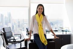 Портрет главного исполнительного директора молодой женщины усмехаясь в офисе Стоковая Фотография