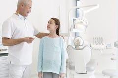 Портрет дантиста говоря с пациентом девушки на зубоврачебной клинике стоковая фотография rf