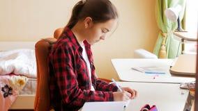 Портрет девочка-подростка делая домашнюю работу в спальне Стоковая Фотография
