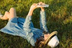 Портрет девочка-подростка 14 лет старый лежать на траве Девушка в шляпе платья, в ее наушниках держит smartphone, слушает к musi Стоковая Фотография