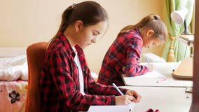 Портрет 2 девочка-подростков делая домашнюю работу дома Стоковое Фото