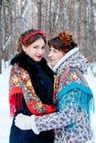 Портрет 2 девушек в славянском стиле в лесе зимы стоя напротив одина другого стоковое фото