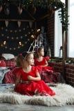Портрет девушек милого thinkfull маленьких двойных около окна и выглядеть внешний Курчавые сестры в красных платьях сидя на пушис стоковые изображения