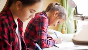 Портрет 2 девушек сидя за столом в спальне и писать домашнюю работу Стоковое Изображение RF