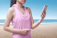 Портрет девушки азиатского бегуна азиатской смотря smartphone Стоковая Фотография RF