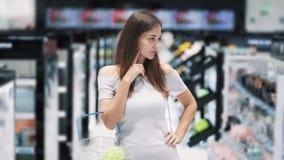 Портрет девушки в косметиках ходит по магазинам думает который продукт, который нужно купить, замедленное движение видеоматериал