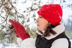 Портрет девушки в красной крышке и теплой куртке в лесе в зиме Стоковое Фото