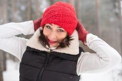 Портрет девушки в красной крышке и теплой куртке в лесе в зиме Стоковое фото RF