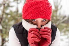 Портрет девушки в красной крышке и теплой куртке в лесе в зиме Стоковая Фотография