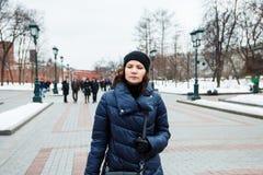 Портрет девушки в пальто на улице в городе на предпосылке людей Стоковые Фотографии RF