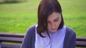 Портрет девушки в парке читая книгу сток-видео