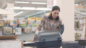 Портрет девушки в рубашке шотландки смотря гриль в магазине акции видеоматериалы