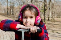 Портрет девушки в теплых наушниках полагаясь на колесе самоката стоковая фотография