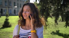 Портрет девушки детенышей усмехаясь кавказской стоя в парке и говоря на smartphone, скроллинге, университете внутри акции видеоматериалы