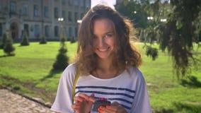 Портрет девушки детенышей усмехаясь кавказской стоя в парке и используя smartphone, перечисляя университет в видеоматериал