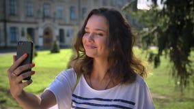 Портрет девушки детенышей усмехаясь кавказской стоя в парке и используя smartphone говоря здравствуйте! к видео- болтовне, делая видеоматериал