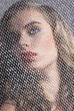 Портрет девушки за сетью повернул на право Стоковое Фото