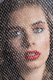 Портрет девушки за сетью смотрит внутри к объективу Стоковое Изображение