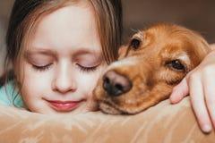Портрет девушки и собаки лежа на софе Стоковое Изображение