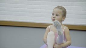 Портрет девушки которая сидит на циновке и протягивает ее ноги в свою очередь во время клуба балета сток-видео