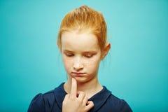 Портрет девушки ребенка с обиденной стороной смотрит вниз, заботливо кладет ее палец к подбородку, выражает заботу или стоковое фото