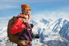 Портрет девушки хипстера фотографа туристской с камерой в солнечных очках и шляпе на фоне снега стоковое изображение
