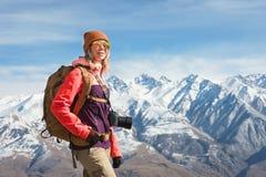 Портрет девушки хипстера фотографа туристской с камерой в солнечных очках и шляпе на фоне снега стоковые фото