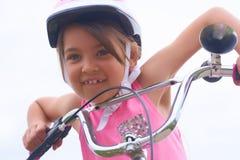 Портрет девушки Cacasian litte в розовом шлеме безопасности управляя ее велосипедом стоковое изображение rf