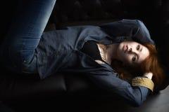 Портрет девушки redhead в рубашке джинсовой ткани и черный бюстгальтер при mehendi лежа на комоде лежа на кресле и руках в волоса Стоковые Фотографии RF