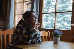 Портрет девушки redhead в шотландке сидя на таблице в кухне Стоковое Фото