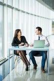 Портрет делового партнера сидя на его аккуратном стеклянном столе перед его компьютером в светящем белом офисе Стоковое Изображение