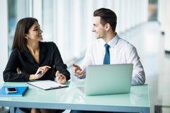Портрет делового партнера сидя на его аккуратном стеклянном столе перед его компьютером в светящем белом офисе Стоковые Изображения
